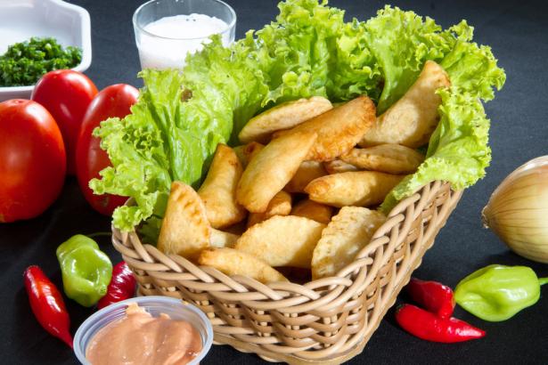 Bolinho de mandioca frito, recheado com linguiça de porco, tomate, cheiro verde