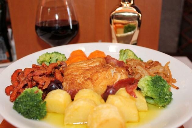 Medalhão de Bacalhau - Lombo de bacalhau com presunto parma, cebola, pimentão vermelho, batatas coradas, brócolis americano e cenoura com molho do chef.